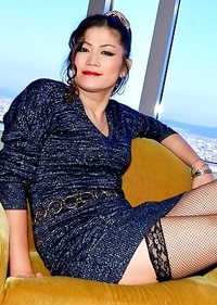 Asian ladyboy Yuki a classy newhalf with legs for days and a tight black dress, stockings, and heels.